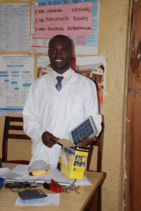 Bless receives a solar lantern donated by Solar Light for Africa.