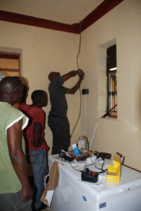 Timothy installing wiring for new refrigerator for medicine and vaccines at the new ward for the Health Centre.