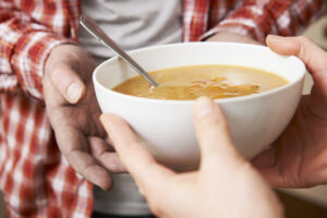 Homeless Man Being Handed Bowl Of Soup By Volunteer